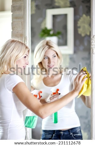 A young woman cleans the a mirror  - stock photo