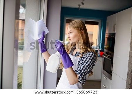 A young woman cleans the window. Rubber gloves on her hands. For cleaning using cleaning fluid and cloth