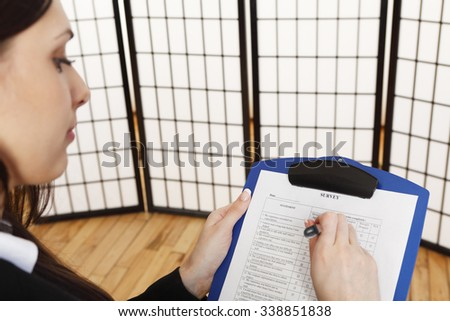 A young woman completing a survey form. - stock photo