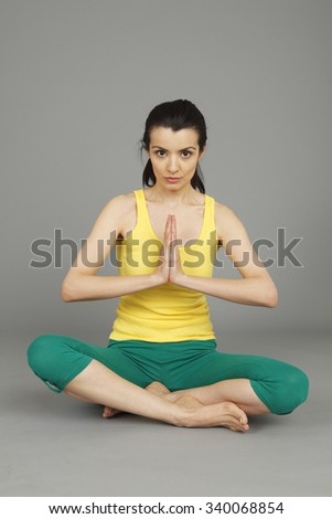 A young woman cross legged with hands together. - stock photo