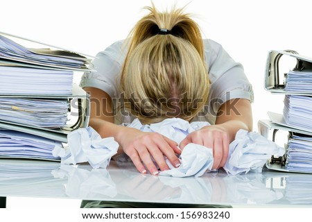 a young woman desperately in office between many file folders and crumpled papier.symbolfoto for stress, burnout and overwork.