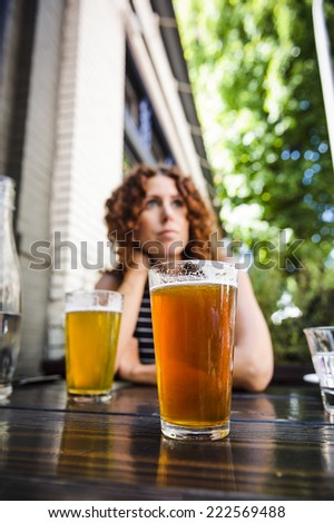a young woman drinking beer at an outdoor pub.  focus is on glass of beer. - stock photo