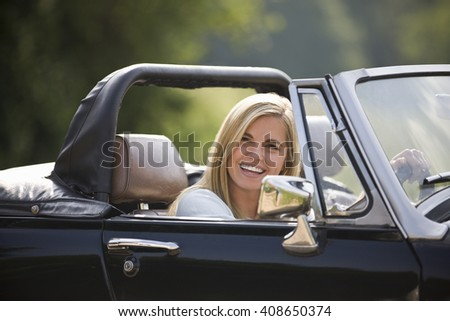 A young woman driving a black sports car