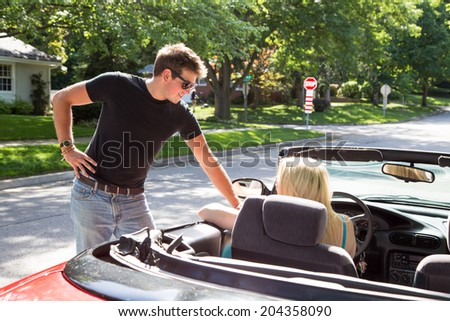 A young woman driving a red convertible stops to talk to a young man on the road in a residential neighborhood. - stock photo