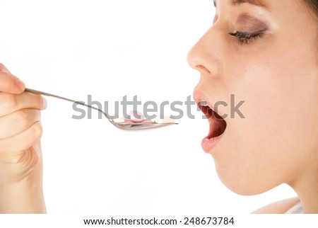 A young woman eating a spoon full of pills