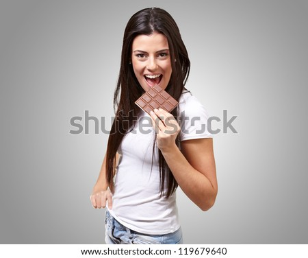 A Young Woman Eating Chocolate Bar On Grey Background - stock photo