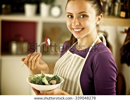 A young woman eating salad in her kitchen . - stock photo