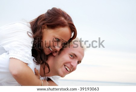 A young woman embraces her lover on a romantic beach setting.