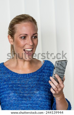 a young woman enjoying a text message she got on her cell phone. - stock photo