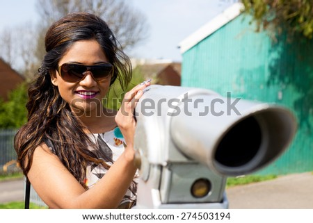 a young woman enjoying a view through a telescope. - stock photo