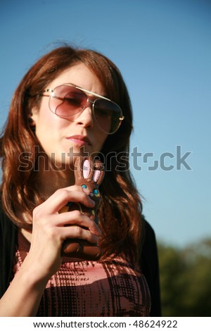 a young woman enjoys eating a chocolate easter bunny - stock photo