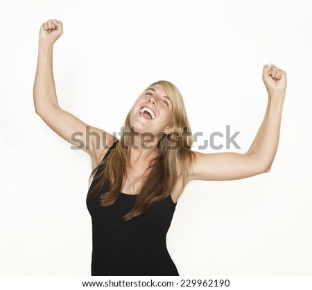 A young woman exults and rejoices. She stretches her arms in the air. white background - stock photo
