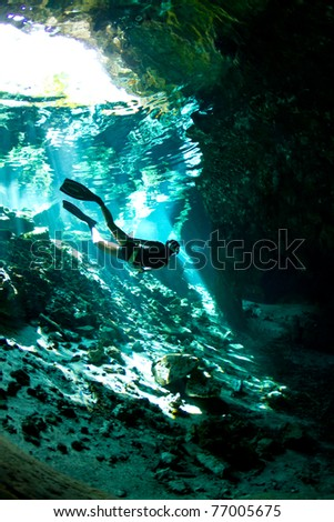A young woman free dives into a Cenote - stock photo