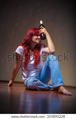 A young woman from a bottle of wine-drinking at home sitting on the floor