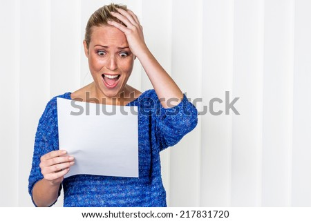 a young woman gets bad news in a letter in the mail - stock photo