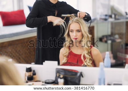 a young woman getting her hair curled by beautician at parlor - stock photo