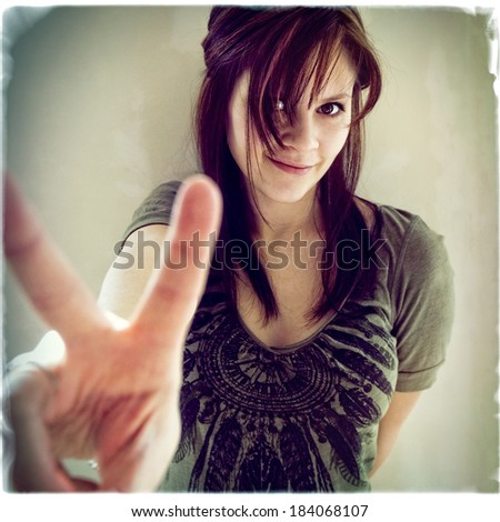 A young woman giving a peace sign with her fingers, instagram style