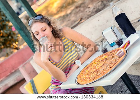 A young woman going to eat pizza - stock photo