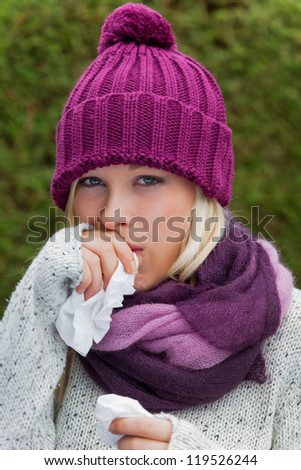 a young woman has a cold and has a cold. autumn is the time for flu, colds and flu - stock photo