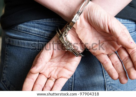 A young woman has been arrested and handcuffed behind her back. - stock photo