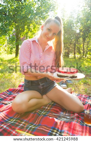 A young woman having a picnic with a cake in the garden.