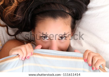 A young woman hiding under a blanket. - stock photo