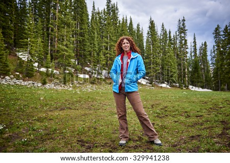 a young woman hiking in the mountains - stock photo