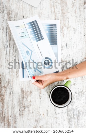 A young woman holding a analytical spreadsheet for her business.  - stock photo