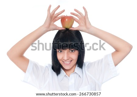 A young woman holding a apple on head