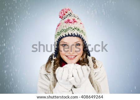 A young woman holding a handful of snow, smiling - stock photo