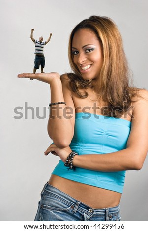 A young woman holding a miniature young man in her hand. - stock photo