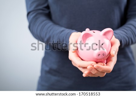 A young woman holding a pink ceramic piggy bank in her hands.