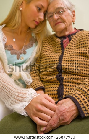 A young woman holding a sick old woman's hand (focus on hands) - part of a series. - stock photo