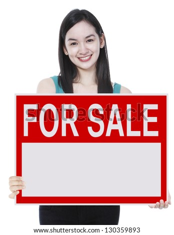 A young woman holding a signboard indicating For Sale