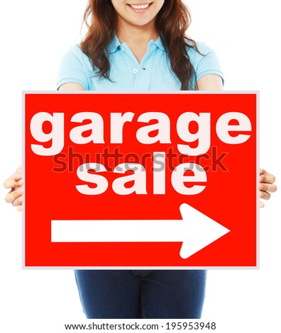 A young woman holding a signboard indicating Garage Sale  - stock photo