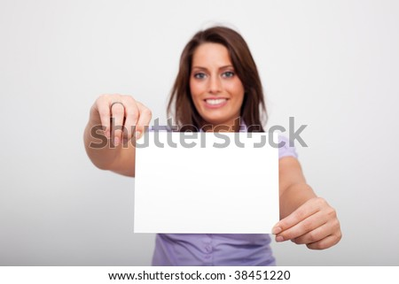A young woman, holding an empty paper in her hands - stock photo