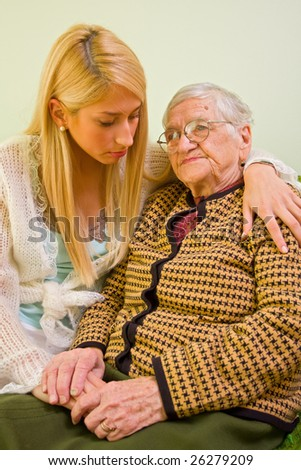 A young woman holding an older one whit love and empathy - part of a series.