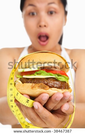 A young woman holding burger with measuring tape around, concept for diet