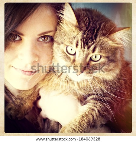 A young woman holding her pet Maine Coon cat, instagram style