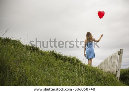 A young woman holds a baloon in the breeze, New Zealand