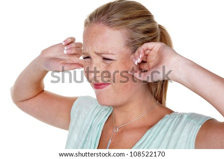 a young woman holds her fingers in her ears. loudness and tinnitus., - stock photo