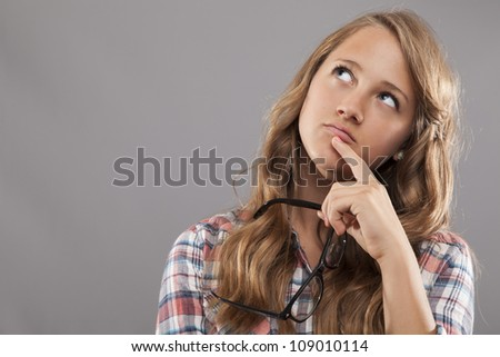 A young woman holds her glasses and looks up as she ponders - stock photo