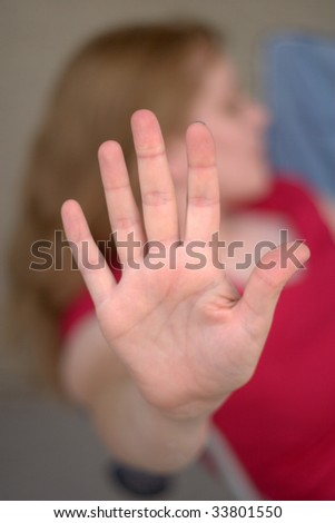 A young woman holds her hand to the viewer looking the other way in a shallow depth of field shot. - stock photo