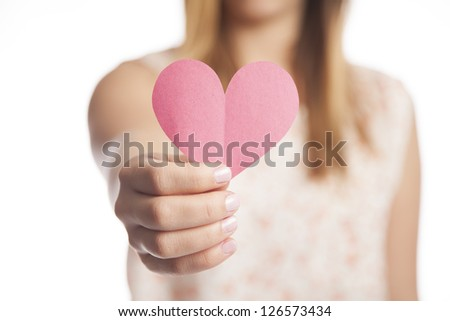 A young woman holds out a cut out construction paper heart. - stock photo