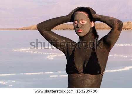 A young woman in a bathing suit is enjoying the natural mineral mud sourced from the Dead Sea,  Israel. - stock photo
