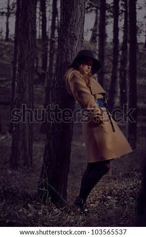 A young woman in a beige coat and hat in the woods