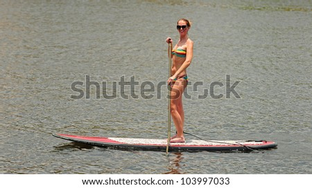 A young woman in a bikini on a paddle board while exercising