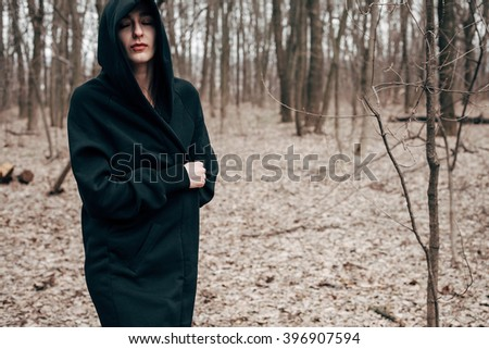 A young woman in a black cloak standing in the woods