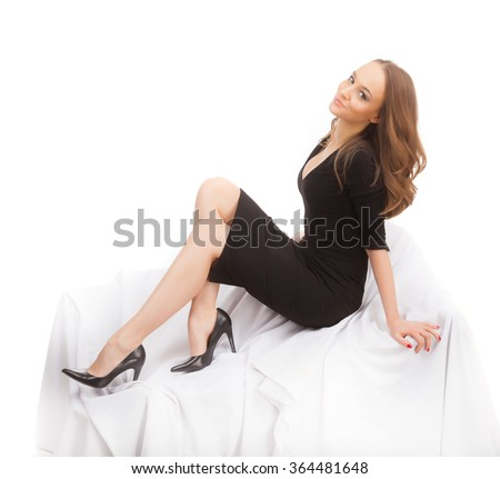 A young woman in a black dress sitting on a white background.