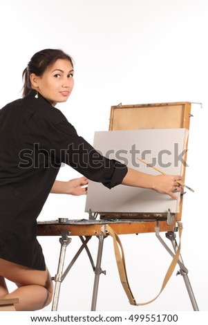 A young woman in a black shirt near easel begins to draw a picture.